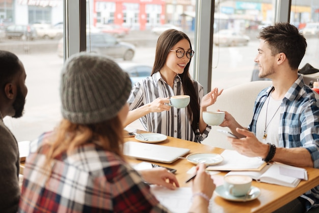 L'ora del tè. ragazza asiatica sorridente felice che ha conversazione piacevole con il suo amico maschio mentre beve il tè al caffè con gli amici.