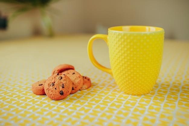Ora del tè, tazza di tè gialla e biscotti sul tavolo.
