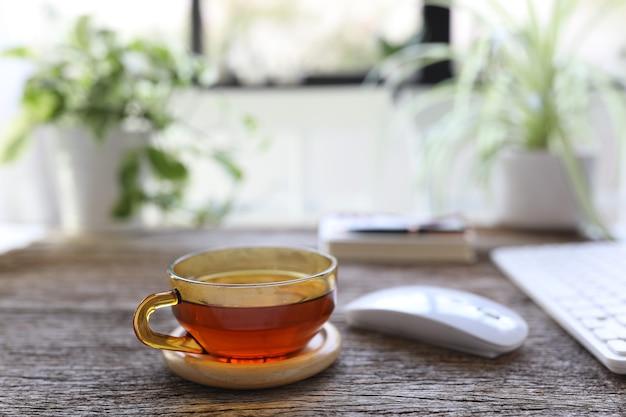Tè in tazza di vetro trasparente sul tavolo di legno con mouse e tastiera