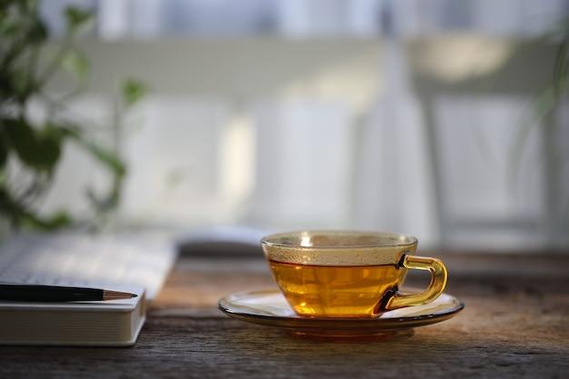 Tè in tazza di vetro trasparente sul tavolo di legno con taccuino e penna