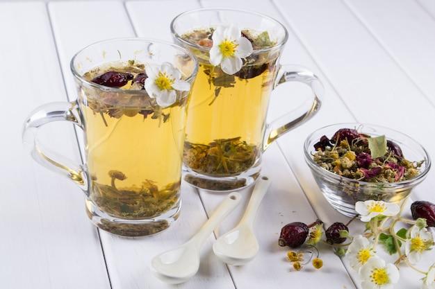 Tè di erbe e fiori utili. due tazze di vetro. ingredienti del tè