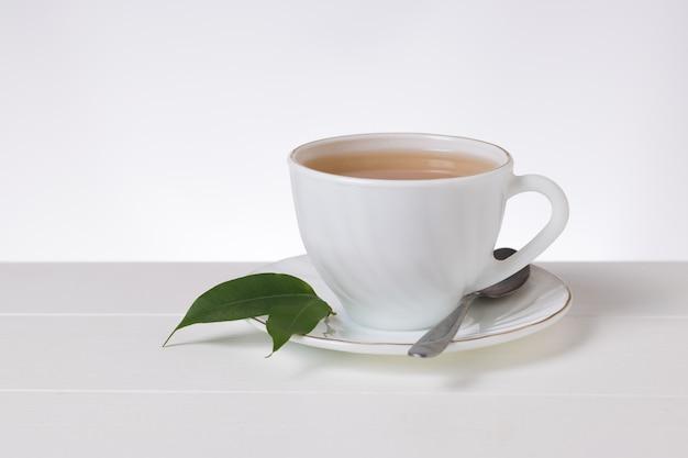 Tè in una tazza di porcellana bianca e un cucchiaio di metallo su un tavolo bianco. una bevanda tonificante utile per la salute.