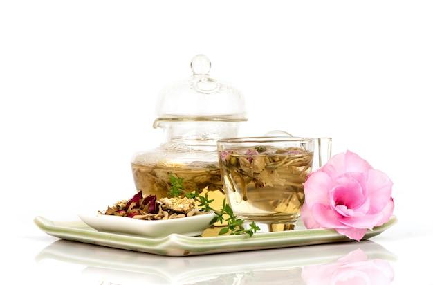 Tè con caprifoglio giapponese essiccato, rosa e fiori di crisantemo isolati su superficie bianca.