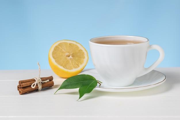 Tè con limone e cannella in una ciotola bianca su un tavolo bianco. una bevanda tonificante utile per la salute.