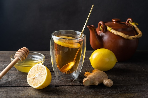 Tè con limone, miele e zenzero in un bicchiere di vetro e una teiera di argilla su una superficie di legno scuro.