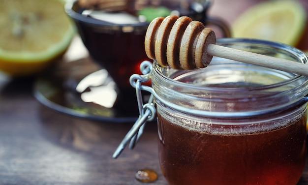 Tè con limone e menta in natura. una tazza di tè caldo alla menta con limone e miele in barattolo. fette di limone e un cucchiaio con miele per il tè caldo.