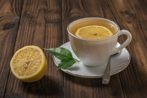 Tè con fette di limone in una tazza bianca su un tavolo di legno. una bevanda tonificante utile per la salute.