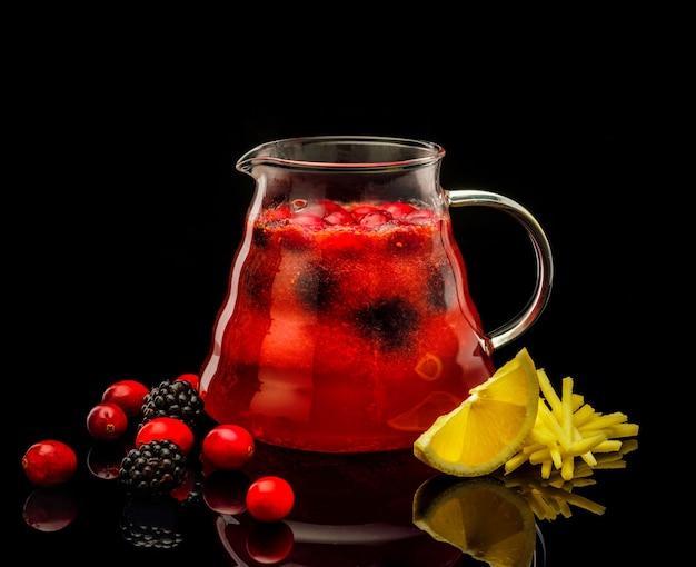 Tè con lime e frutti di bosco freschi in una brocca su un nero