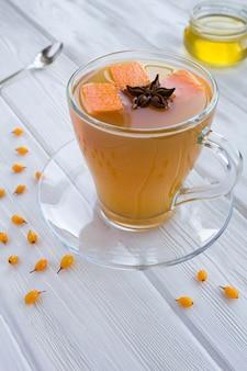 Tè con zucca, olivello spinoso e spezie nella tazza di vetro sul tavolo di legno bianco.