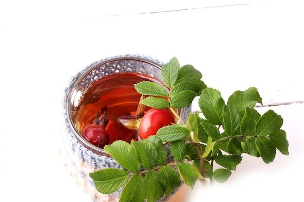 Tè con rosa canina e foglie di legno sfondo bianco vitamina c inverno autunno a maglia tazza