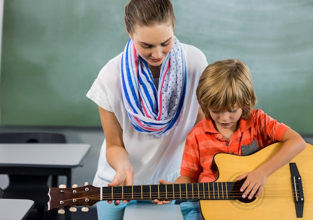 Insegnante che aiuta boyto a suonare la chitarra in aula