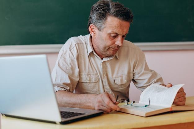 Insegnante che legge attentamente il libro di testo
