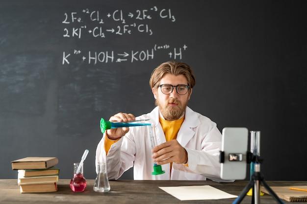 Insegnante di chimica che mostra la reazione chimica durante la miscelazione di due sostanze liquide durante il lavoro di laboratorio online davanti alla fotocamera dello smartphone