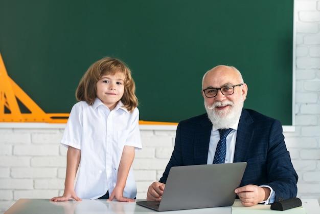 Insegnante e bambino. di nuovo a scuola. istruzione e apprendimento a scuola. scolaro in aula. vecchio insegnante e giovane allievo.