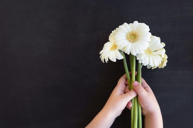 Giornata dell'insegnante. le mani del bambino tengono il mazzo di fiori sulla lavagna