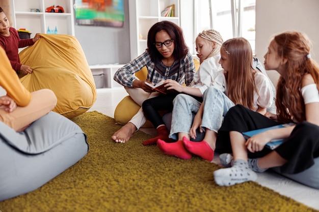 Insegnante con gli occhiali seduto su un pouf e leggendo per i bambini in classe