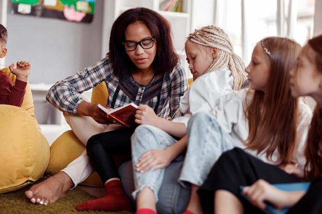 Insegnante con gli occhiali seduto su un pouf e leggendo per i bambini a scuola