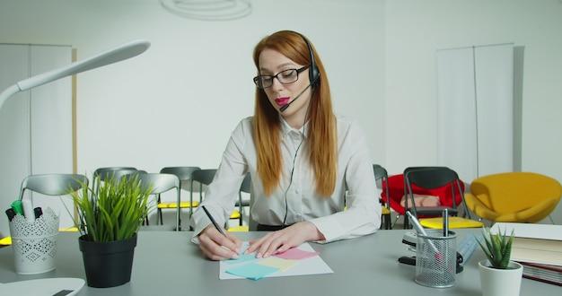 Insegnante in cuffia con microfono insegnamento virtuale guarda la webcam impartisce lezione a distanza.
