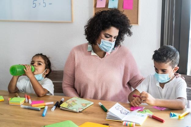Insegnante che aiuta i bambini all'interno della scuola materna durante l'epidemia di coronavirus - focus on boy face