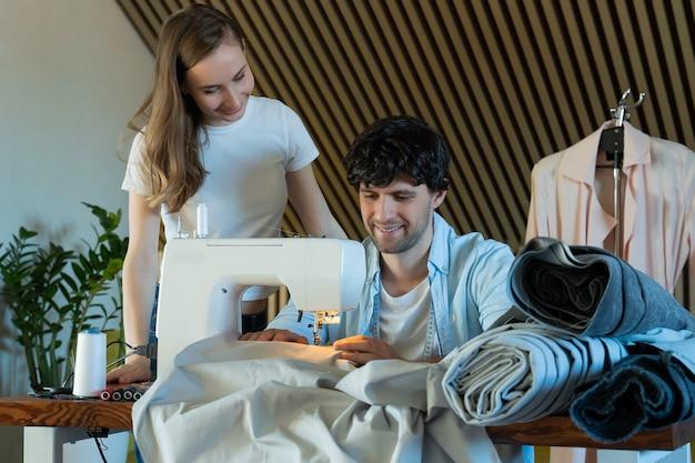 Insegnante che aiuta uno studente di moda che impara a usare la macchina da cucire donna insegna al suo uomo studente a imparare a disegnare e cucire