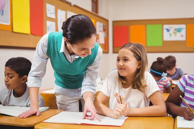 Insegnante che aiuta una bambina durante le lezioni