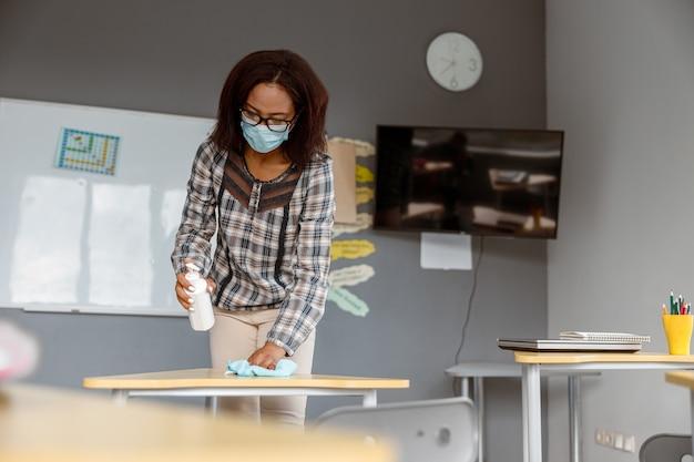 Insegnante che tiene disinfettante e sta in piedi in classe