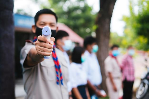 Insegnante che tiene la temperatura della pistola del termometro a infrarossi