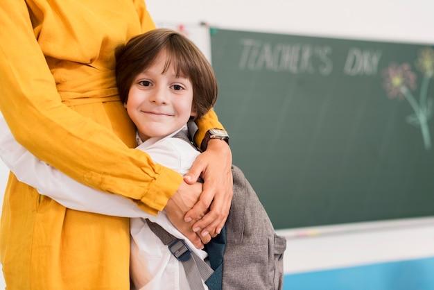 Insegnante che abbraccia uno studente con lo spazio della copia