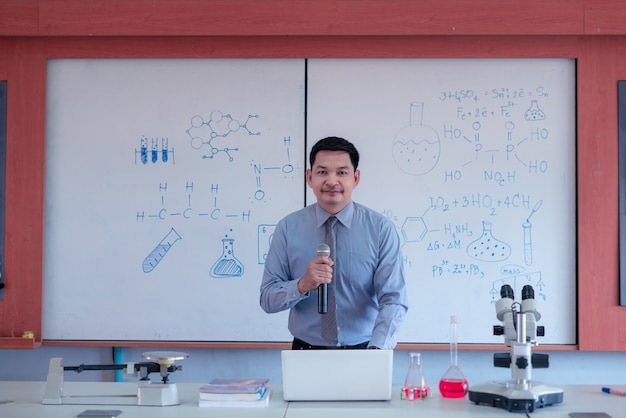 L'insegnante sta insegnando lezioni di scienze online durante il blocco a causa della pandemia di covid-19. concetto di felice giornata degli insegnanti
