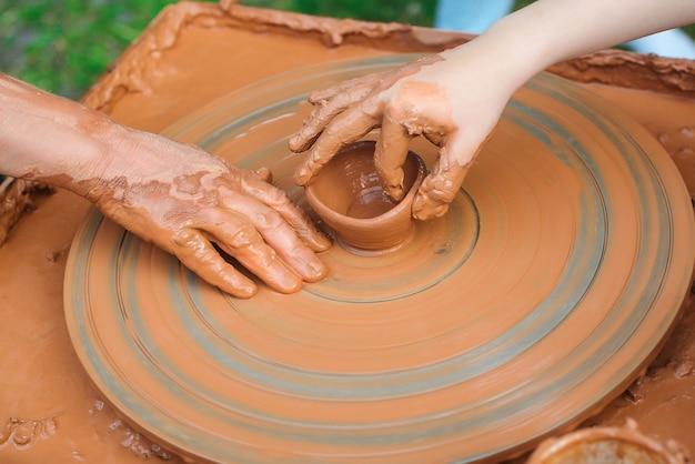 Insegnante e bambino che fanno vaso di ceramica. vasai e mani di bambini. laboratorio di ceramica all'esterno. maestro che insegna al bambino a creare sul tornio. la nonna insegna alla nipote la ceramica. modellazione dell'argilla.