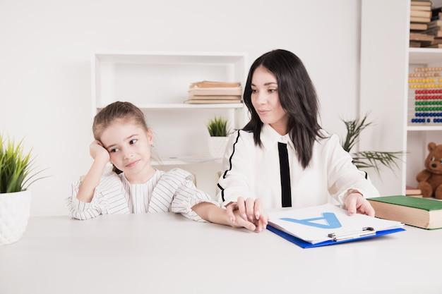 Insegnante e bambina che lavorano insieme su una pronuncia in classe.