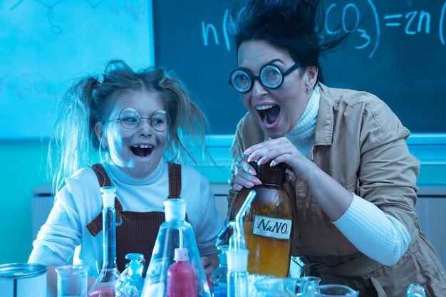 Insegnante e bambina durante la lezione di chimica mescolando prodotti chimici