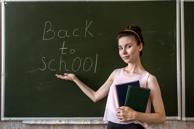 Insegnante vicino alla lavagna, scritto di nuovo a scuola, concetto di educazione