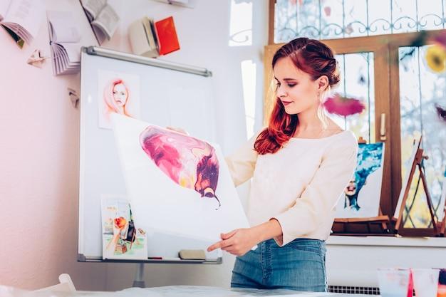 Insegnante vicino alla lavagna. bella giovane insegnante d'arte in piedi vicino alla lavagna con pittura in marmo