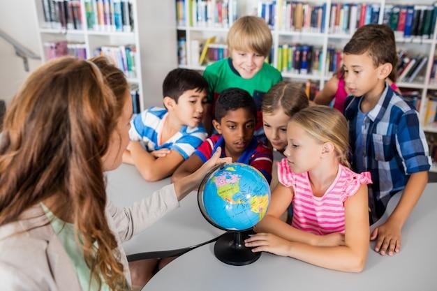 Insegnante e alunni guardando un globo