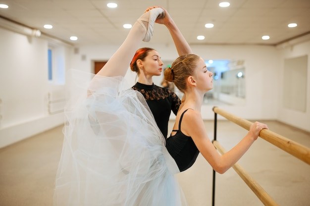 Insegnante che prova con la giovane ballerina alla sbarra in classe