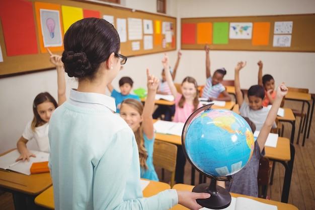 Insegnante che mostra agli alunni un globo