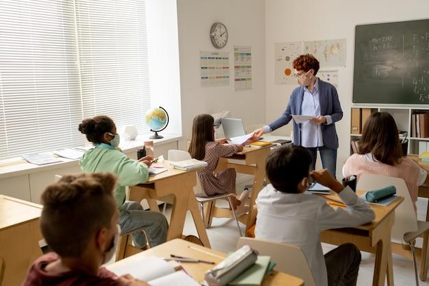 Insegnante di abbigliamento casual intelligente che passa documenti agli scolari per il lavoro individuale