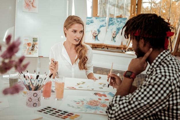 Insegnante e studente. bionda esperta insegnante d'arte che parla con il suo talentuoso studente