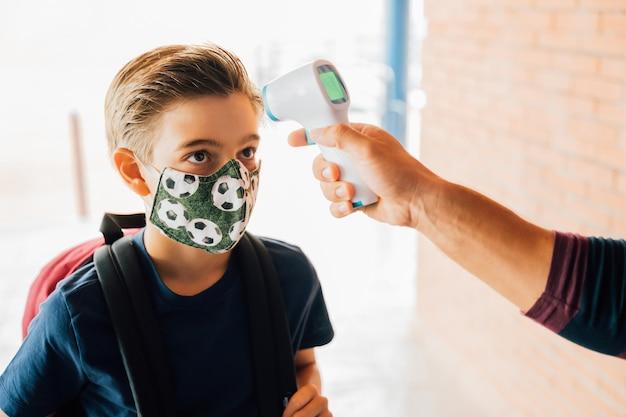 Insegnante che misura la temperatura di un ragazzo con un termometro durante la pandemia covida.