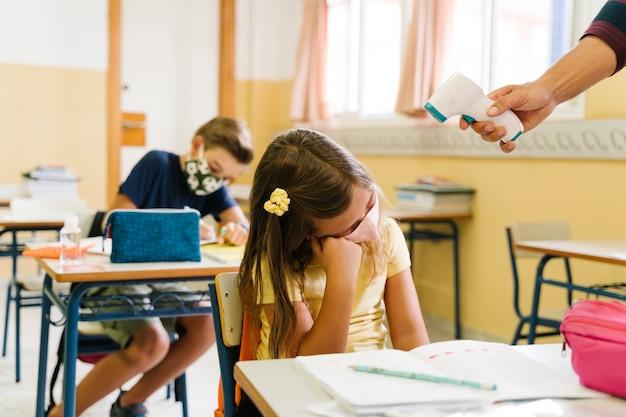 Insegnante che misura la temperatura di una ragazza in classe con un termometro durante la pandemia covida.