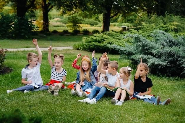 Un insegnante insegna a una classe di bambini in un parco all'aperto. ritorno a scuola, apprendimento durante la pandemia.