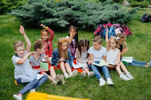 Un insegnante insegna a una classe di bambini in un parco all'aperto