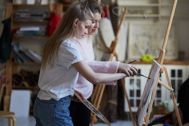 L'insegnante insegna a una giovane ragazza a dipingere su tela nella stanza