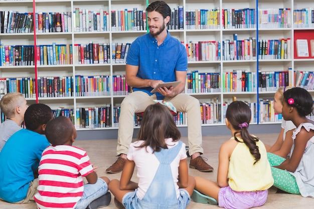 Bambini d'istruzione dell'insegnante sulla compressa digitale in biblioteca