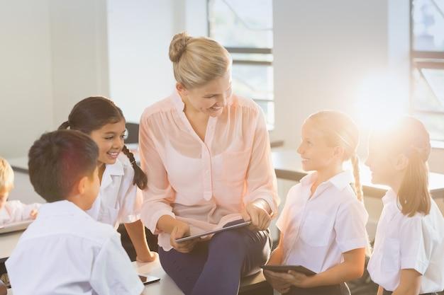Insegnante insegnare ai bambini su tavoletta digitale