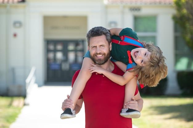 Insegnante in maglietta e scolaro carino con zaino vicino all'uomo del parco della scuola e porcellino bambino stupito eccitato...