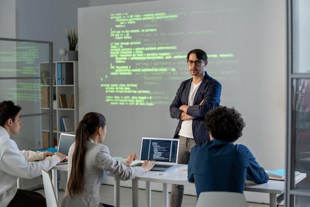 Insegnante universitario con le braccia incrociate sul petto che fa presentazione a un gruppo di studenti in piedi davanti al grande schermo