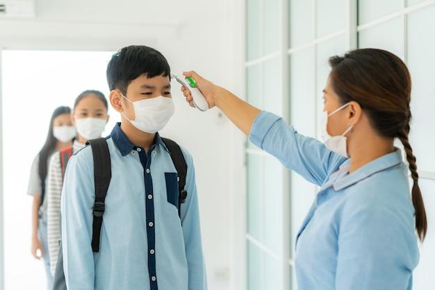 Insegnante che utilizza uno studente di screening della temperatura del termometro per la febbre contro la diffusione di covid-19