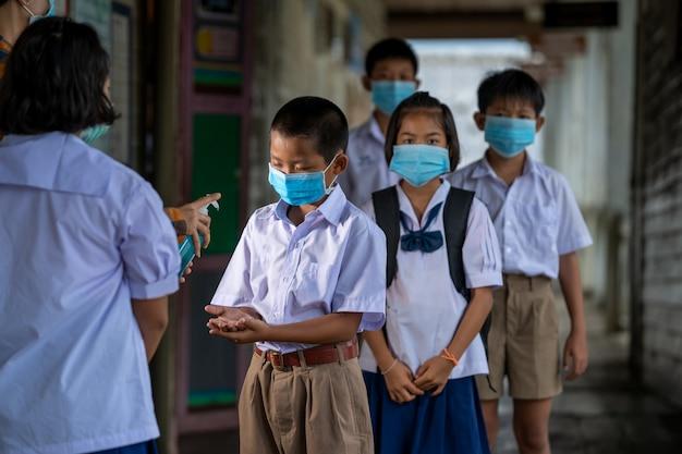 L'insegnante indossa una maschera protettiva per proteggere contro il covid-19 e tratta le sue mani con gli studenti con antisettico in classe, scuola elementare, apprendimento e concetto di persone.